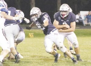 North Branch's Drake Deshetsky looks for a gap as Colton Law lays a block against Croswell-Lexington in the district semifinal on Nov. 6. Photo by Kylee Richardson
