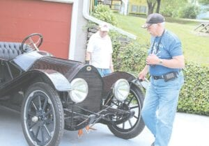 Kent Copeman (left), president of the Hadley Township Historical Society, and David Beckley examine the 1913 Regal on loan to the museum this summer.  Beckley coordinates vehicle exhibits at the museum.