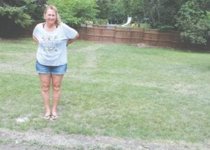 Debbie Maxfield stands in front of a lot that could've been under water during her daughter's wedding reception Saturday evening if it weren't for the Lapeer DPW that brought sandbags to channel rain runoff away from where a tent was located. Photo by Jeff Hogan