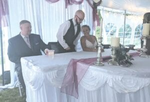 Chris and Nicole Cifuentes kept dry under a tent during their wedding reception Saturday evening in Lapeer. Photo courtesy Debbie Maxfield