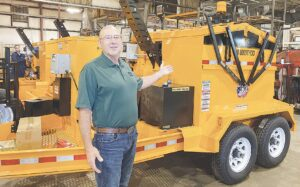 Cliff Cameron, President of KM International, presents one of his company's asphalt repair machines.  Photo by Wes Smith